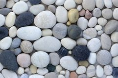 Group of white, grey and black pebbles, one by ony, simplicity stone background. Flat lay texture in daylight royalty free stock photos