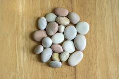 Group of white, grey and light brown stones on wooden background, pebbles beach, circle mandala shape