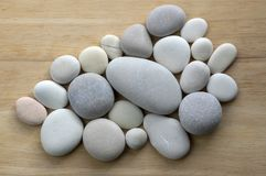 Group of white and grey pebbles, one by ony, simplicity stone background, flat lay texture in daylight. On wooden background stock image
