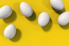 Group of six white eggs on yellow background stock photography