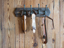 Group of white old ice skates hanging on a wooden wall. Group of white old ice skates  made of wood iron and leather hanging on a wooden wall Stock Photography