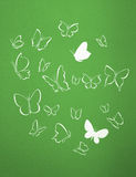 Background of white silhouettes butterflies flying. Group of white silhouettes butterflies flying over a green background Royalty Free Stock Photos