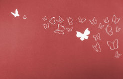 Background of white silhouettes butterflies flying. Group of white silhouettes butterflies flying over a red background Royalty Free Stock Photography
