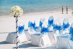 A group of white spandex chairs cover with blue organza sash for beach wedding venue setup. The random white spandex chairs cover with blue organza sash Stock Photo