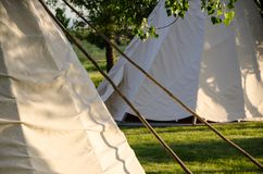 Group of Tipis Standing Among the Trees. Group of White Tipis Standing Among the Trees stock photography