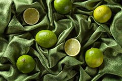Group of whole and cut fresh limes on green satin Stock Photo