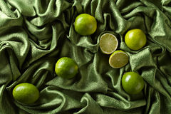 Group of whole and cut fresh limes on green satin Stock Photography