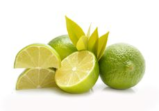 Group of whole and cut fresh limes with leaves. On white Royalty Free Stock Photography