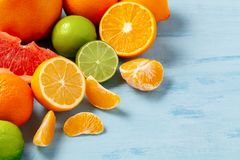 Group of whole and sliced citrus fruits - tangerines, lemons, limes, oranges, grapefruits on the surface of the blue stock photography