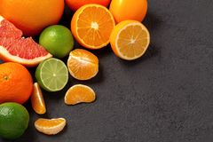 Group of whole and sliced citrus fruits - tangerines, lemons, limes, oranges, grapefruits on the surface of the dark stock images