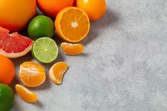Group of whole and sliced citrus fruits - tangerines, lemons, limes, oranges, grapefruits on the surface of the gray stock images