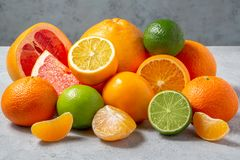 A group of whole and sliced citrus fruits - tangerines, lemons, limes, oranges, grapefruits on the surface of a gray stock images