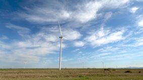 group of wind power generating mills in perspective. Blue sky with clouds