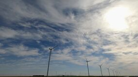 group of wind power generating mills in perspective. Wide sky with clouds. Copy space