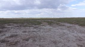 Group of wind turbines in the background of parched land under the blue sky. With white clouds stock video