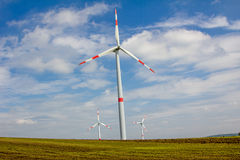 Group of windmills, agains blue sky with clouds Stock Photos