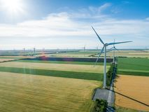 Group of windmills for electric power production in the agricultural fields. Aerial view royalty free stock photo