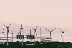 Group of windmills and solar panels for electric power production and oil rigs on coast.  stock images