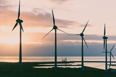 Group of windmills and solar panels for electric power production and oil rigs on coast.  stock photography