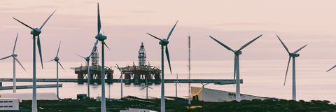 Group of windmills and solar panels. For electric power production and oil rigs on coast royalty free stock photography