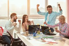 Group of winners celebrate victory or great success. Positive multi-ethnic team satisfied with result, won profitable contract. Friendly people of different Stock Photography