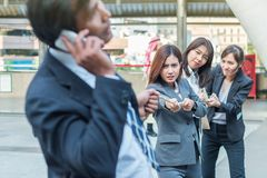 Group of woman pulling a rope competing with a businessman. Group of women pulling a rope competing with a businessman royalty free stock images