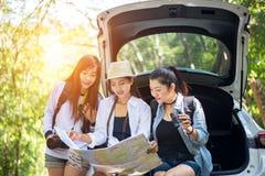 Group woman traveler sitting on hatchback car Stock Photos