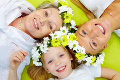 Group of women. Portrait of grandmother, mother, girl with flowers lying on green floor Royalty Free Stock Images