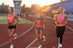 Group of women athletes running together in stadium. Group of women athletes running together in stadium Royalty Free Stock Image