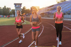 Group of women athletes running together in stadium. Group of women athletes running together in stadium Royalty Free Stock Images