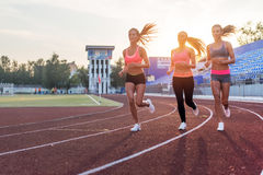 Group of women athletes running together in stadium. Stock Images