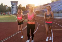 Group of women athletes running together in stadium. Group of women athletes running together in stadium Stock Images