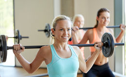 Group of women with barbells exercising in gym. Fitness, sport, training and lifestyle concept - group of happy women with barbells exercising in gym Stock Photo
