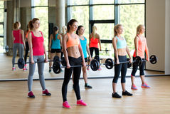 Group of women with barbells in gym. Fitness, sport, training and lifestyle concept - group of women with barbells in gym Royalty Free Stock Photography