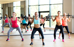 Group of women with barbells in gym. Fitness, sport, training and lifestyle concept - group of women with barbells in gym Royalty Free Stock Image