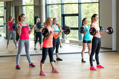 Group of women with barbells in gym. Fitness, sport, training and lifestyle concept - group of women with barbells in gym Stock Photography