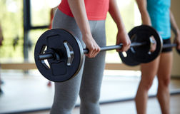 Group of women with barbells working out in gym. Fitness, sport, training, people and lifestyle concept - group of women with barbells flexing muscles in gym Stock Photography
