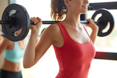 Group of women with barbells working out in gym. Fitness, sport, training, people and lifestyle concept - group of women with barbells flexing muscles in gym Stock Photos