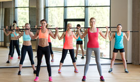 Group of women with bars in gym Stock Images