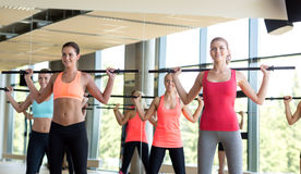 Group of women with bars in gym. Fitness, sport, training, gym and lifestyle concept - group of women with bars in gym stock images