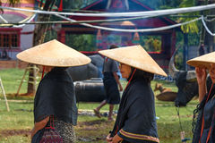 Group of women in black and conical straw hats  at funeral ceremony. Tana Toraja Stock Photos