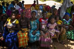 Group of women and children at a community meeting in the village of Mandina Mandinga in the Gabu Region. Gabu Region, Republic of Guinea-Bissau - February 7 royalty free stock photo