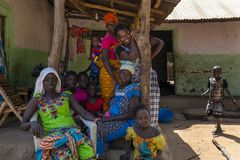 Group of women and chldren in front of a home in the village of Mandina Mandinga in the Gabu Region. Gabu Region, Republic of Guinea-Bissau - February 7, 2018 stock images