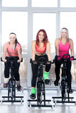 Group of women cycling in gym. Fitness practice, group of three fit beautiful happy females cycling in sports club, doing cardio exercises for slimming, warming Stock Image