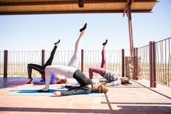 Group of women doing one leg bridge pose. Side view of young women practising one legged bridge yoga pose in fitness center Royalty Free Stock Photos