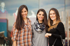Group of women doing some shopping. Portrait of a group of three female friends standing outside a clothing store in a shopping center Stock Images