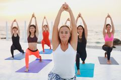A group of women doing yoga at sunrise near the sea. The group of women doing yoga at sunrise near the sea Stock Photos