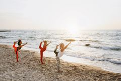 A group of women doing yoga at sunrise near the sea. The group of women doing yoga at sunrise near the sea Stock Images