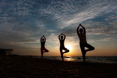 A group of women doing yoga at sunrise near the sea. The group of women doing yoga at sunrise near the sea Stock Photography