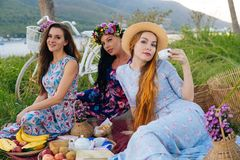 Women enjoying picnic in the countryside - Three girls on vacation having fun. Group of women enjoying picnic in the countryside - Three girls on vacation Stock Photos